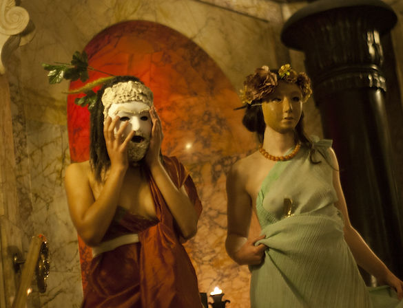 Two masked people drssed in Ancient Greek costume
