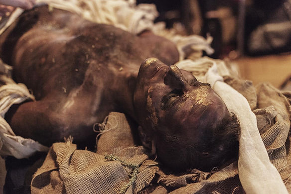 Model lying down painted as Ancient Egyptian mummy