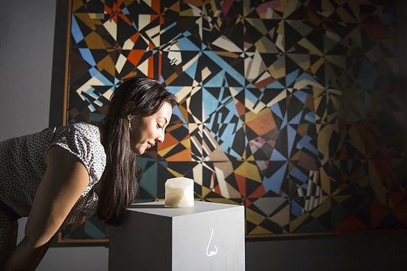 Woman sniffing scented object in front of gallery painting