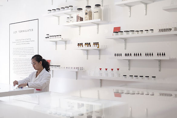 Lab technician in front of shelves in beauty laboratory installation
