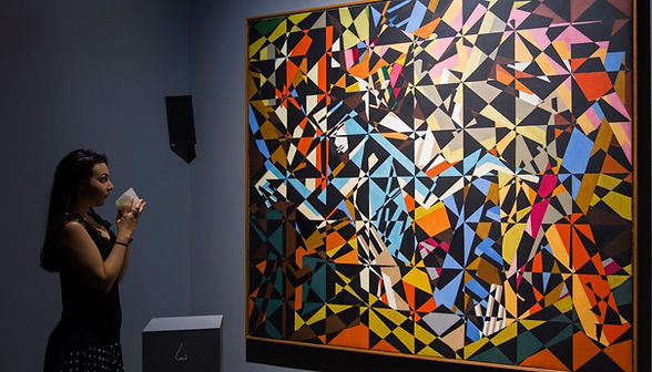 Woman smelling aroma while looking at abstract painting