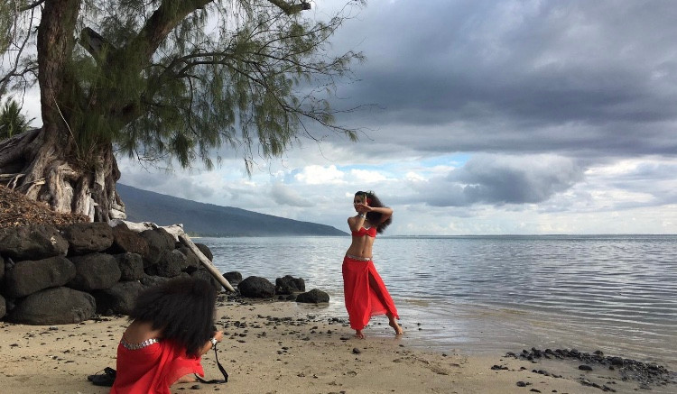 In this photo, a woman dances before a scenic seascape. We see the sand, ocean and a tree in the background, while the dancer makes an arm gesture crossing one hand over the other, palms flat.