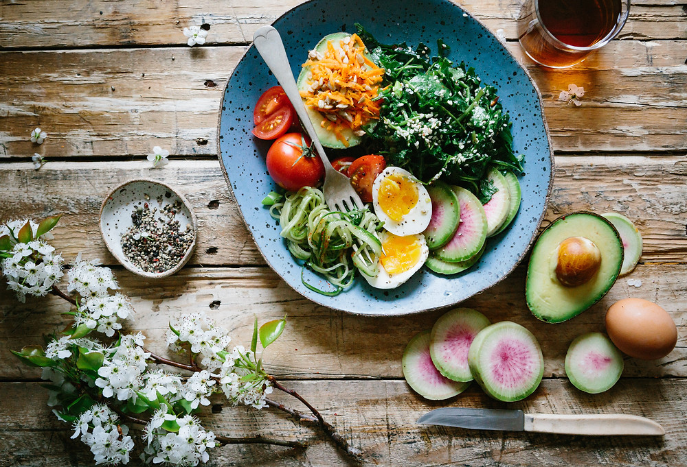 Image of salad with tomato, avocado and egg in a bowl laid out with flowers on on a pale wood table