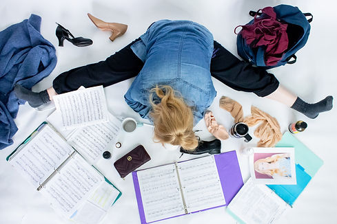 I photo from above of Ali stretching in in a straddle, surrounded by audition things.