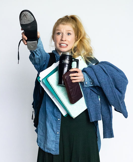 Ali, a blonde, blue eyed woman with her hair in a high pony and an anxious look on her face has her arms full and is frantically waving a tap shoe in the air.