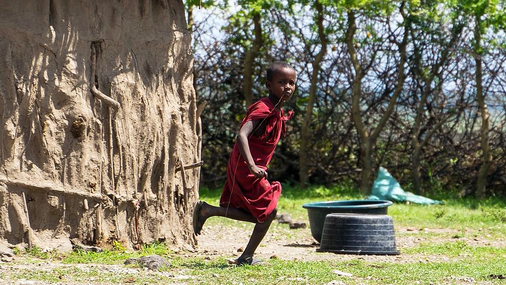Afriški deček z hišo iz blata v ozadju