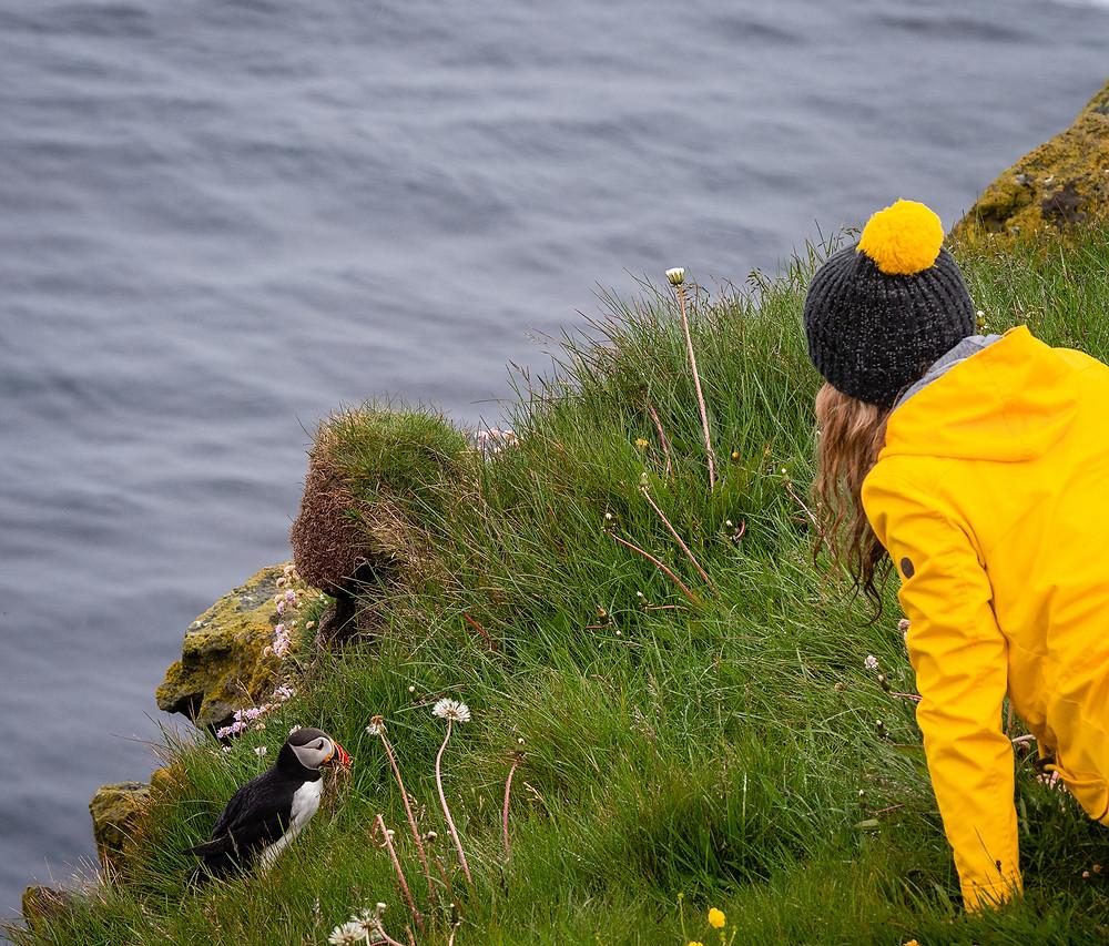 Dekle opazuje njorko na robu pečine