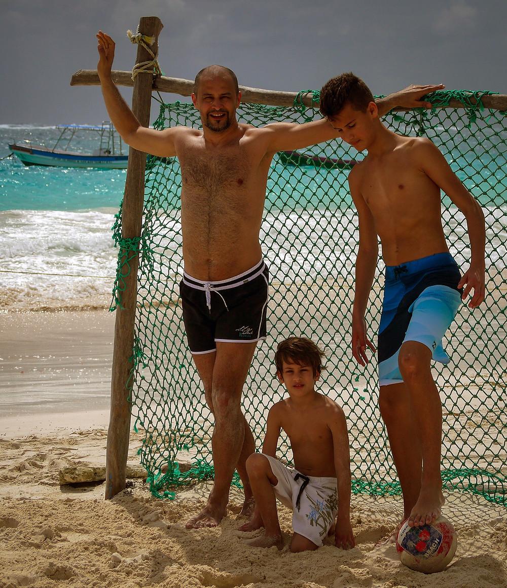 Moški in dva fanta pred nogometnim golom z morjem v ozadju