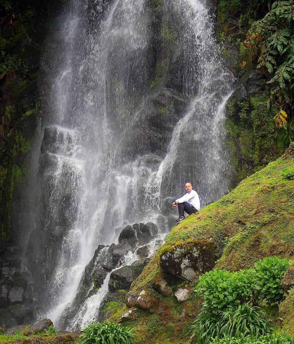 Fant sedi na zelenem griču pred slapom