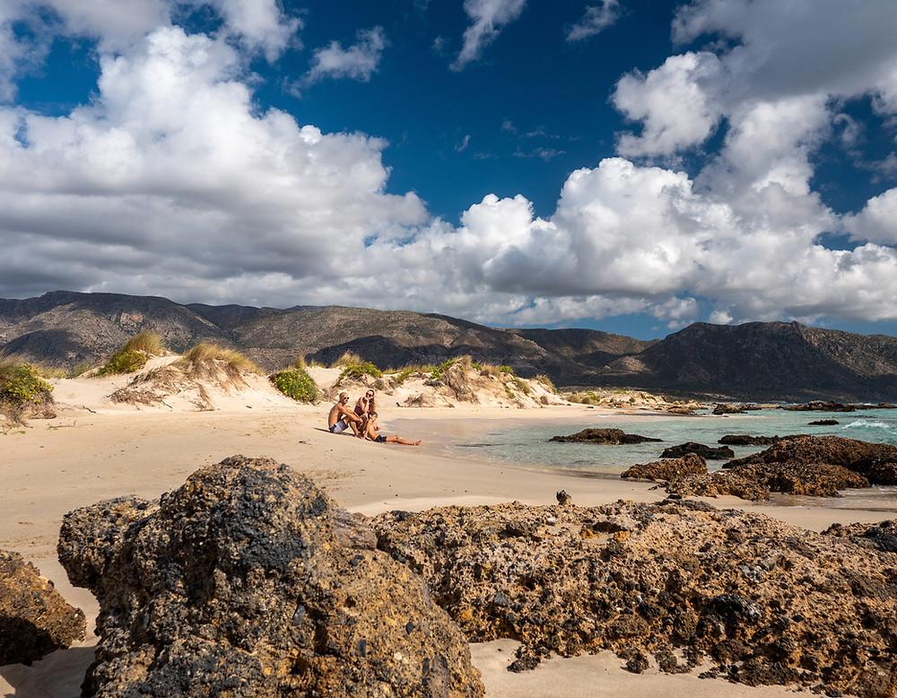 Družina na peščeni plaži s kamenjem v ospredju