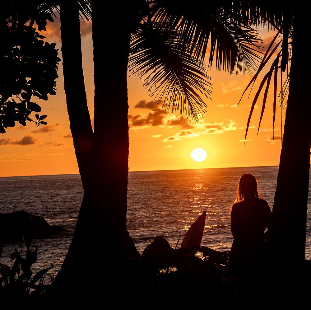 žareče sonce zahaja za obzorje z dekletom, ki ga opazuje