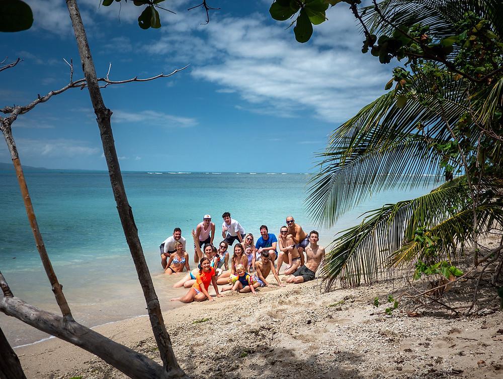 skupina ljudi na plaži s turkiznim morjem v ozadju