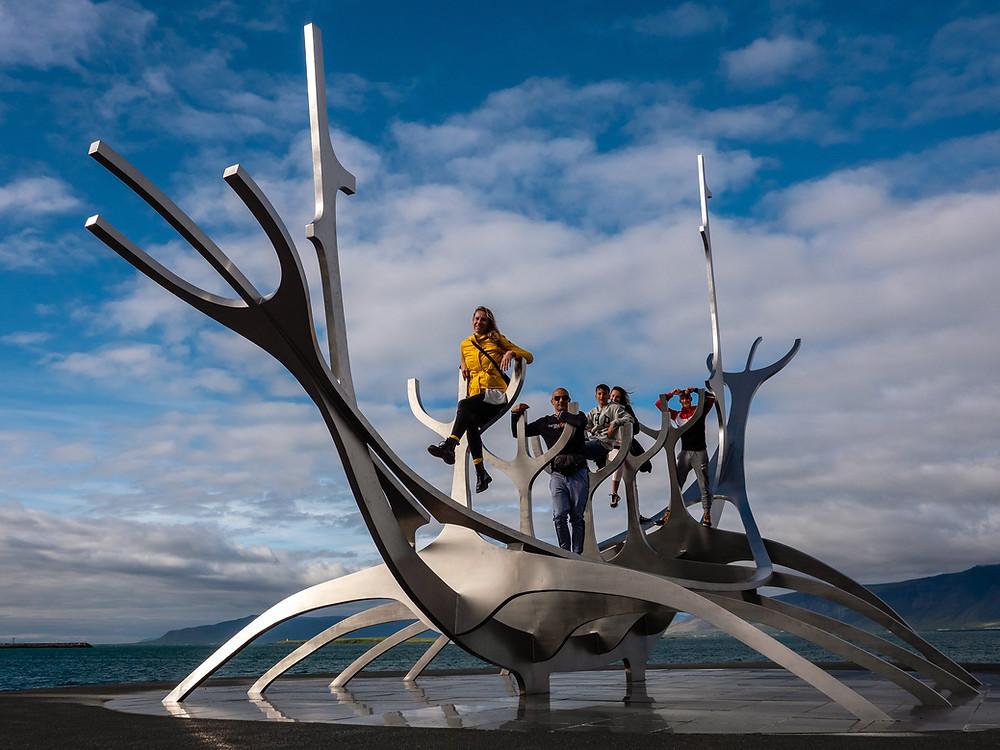 pet ljudi na jekleni skulpturi z morjem in nebom v ozadju
