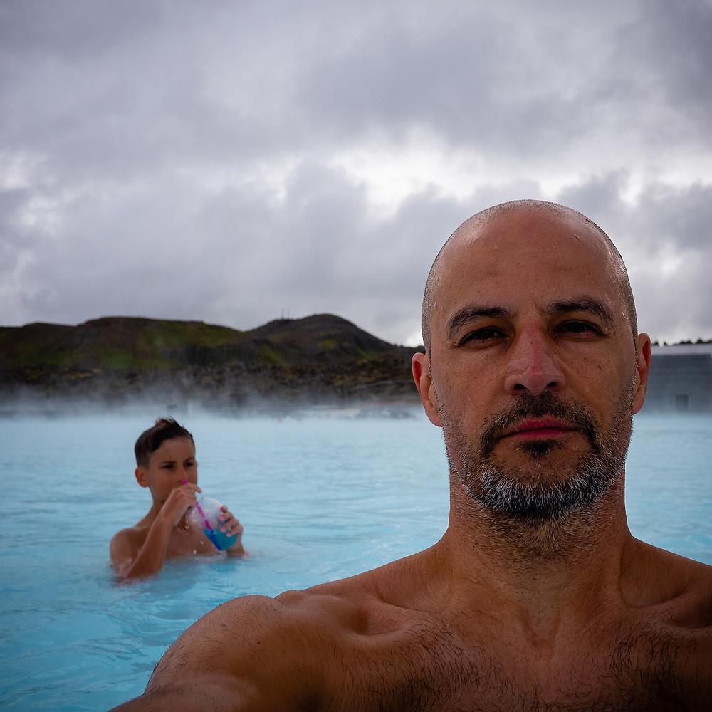 moški dela selfie v bazenu z otrokom v ozadju
