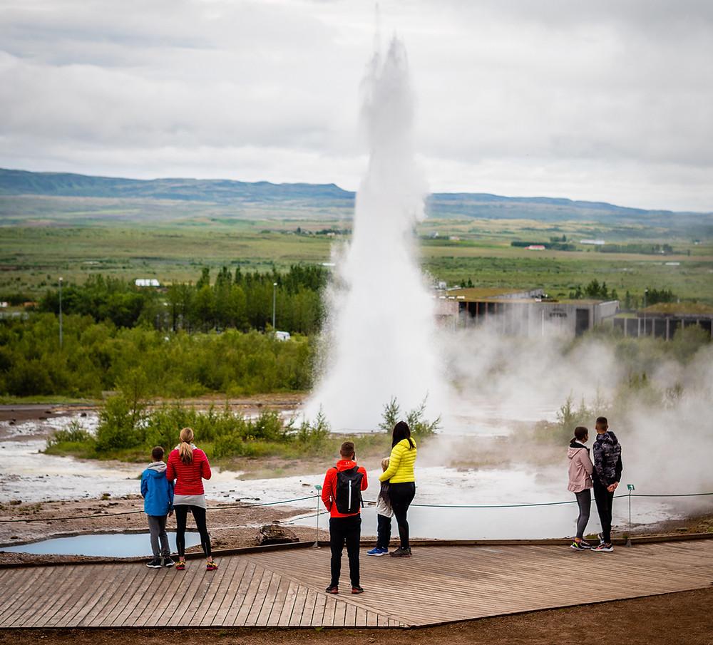 Skupin ljudi opazuje izbruh gejzirja