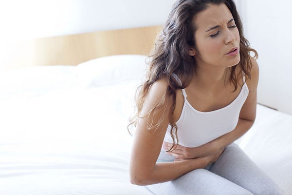 woman-on-bed-with-cramps-623683731-59809