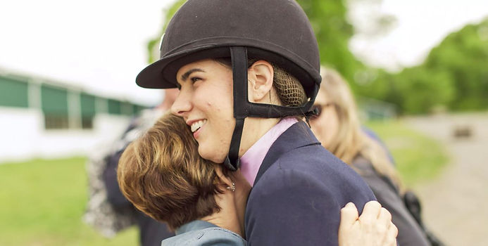 Image: A parent hugging a rider.