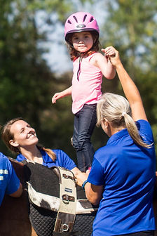 Image: A little girl standing up on top of a horse assisted by side-walkers.
