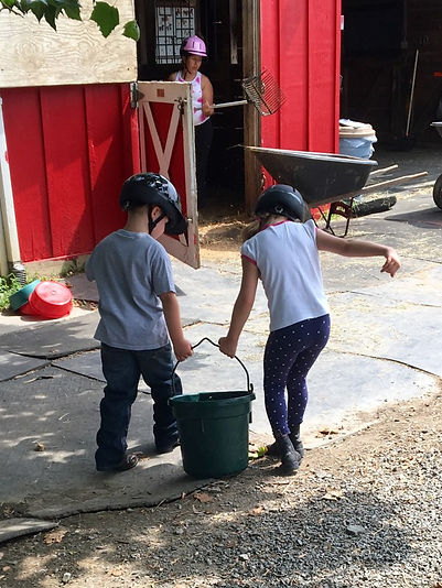 Image: Two children carrying a water bucket towards a barn stall.