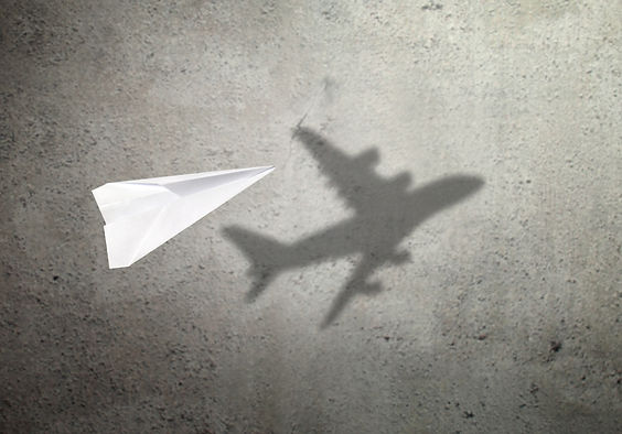Paper plane in mid flight with shadow of