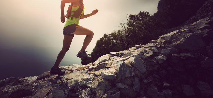 woman trail runner running on the great wall top of mountain.jpg