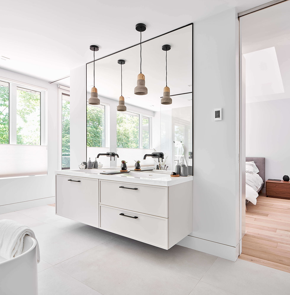 Photo of Westbourne home. A modern all white bathroom, with large bright window, large wall mirror and black faucets.