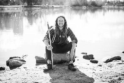 Jonathon Stalls sitting next to lake with walking stick