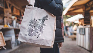 Close up of person holding tote bag with illustrated bird and floral illustration that says 'I am enough'