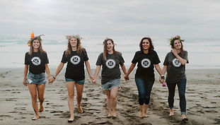 5 women hold hands on the beach.