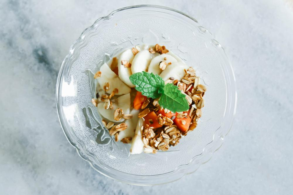 Raw oat and flax seed muesli, made with coconut milk and ginger, and topped with papaya, bananas, and homemade granola.