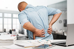 Businessman with back pain an office. Pa