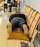 Man sleeping on airport seats
