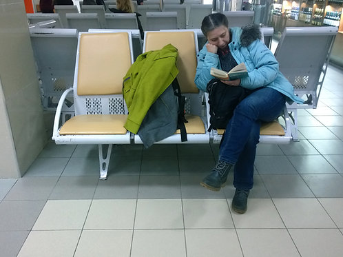 Woman-Reading-in-Airport-Waiting-Area-Family-in-New-York-Tours