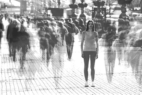 A woman stands alone in a crowd