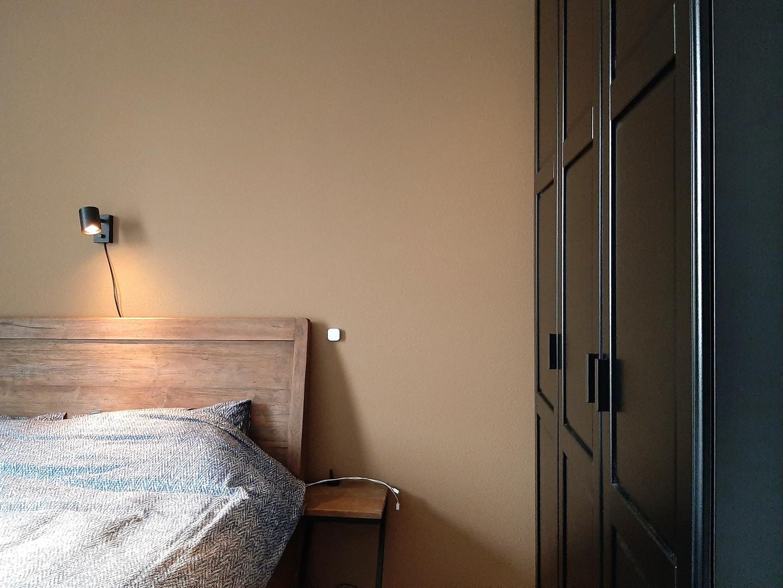 slaapkamer houten bed en zwarte kast - warm en natuurlijk