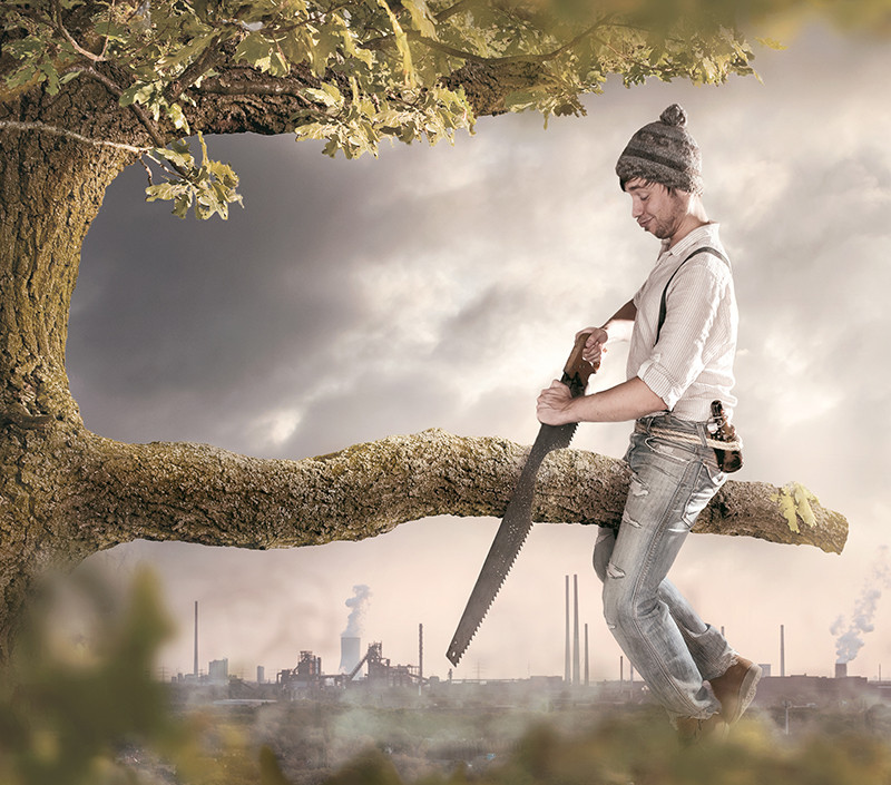 A man dangerously cutting the branch he's sitting on using a saw