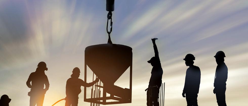 Pracownicy budowlani o zachodzie słońca