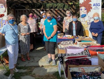 Donated fabrics and members in a garden patio area