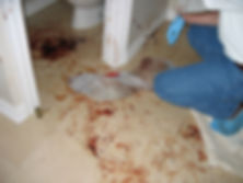 biohazard technician leaning down toward blood pool, bloody towels, blood droplets on tile
