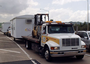 Flatbed tow truck transporting an Office Trailer