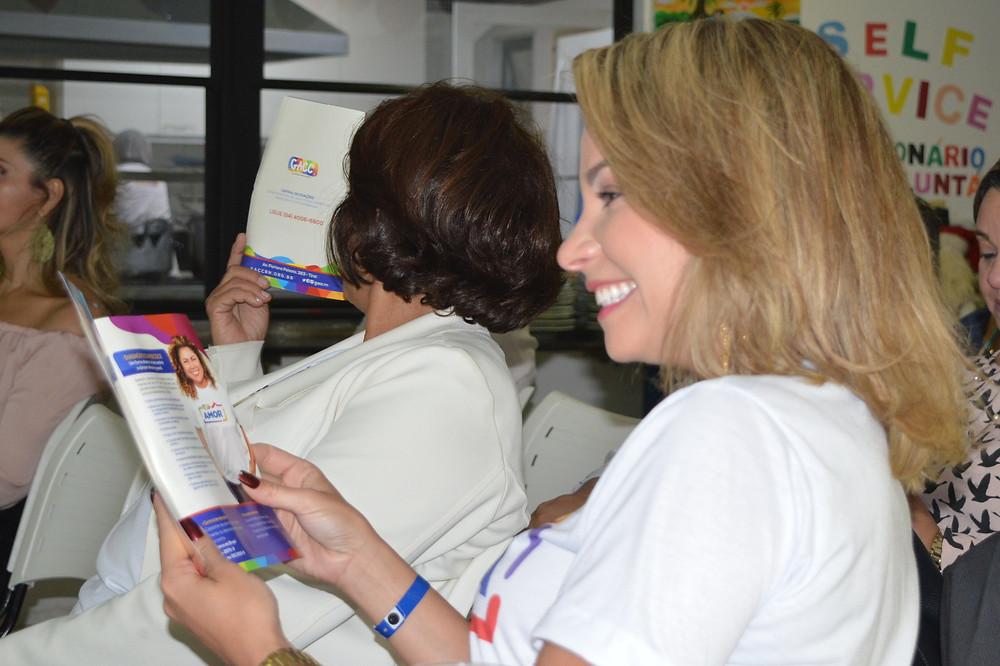 Manu Pessoa com folder da campanha que também terá fotos da apresentadora