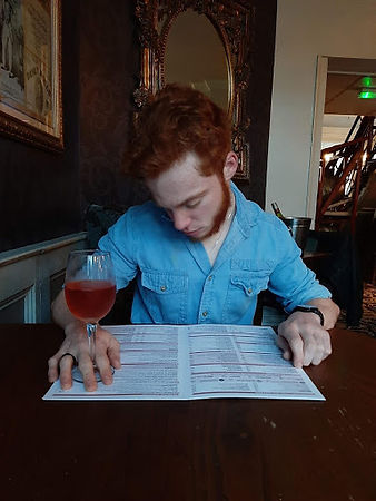 Charlie is sat looking t a menu with a glass of wine