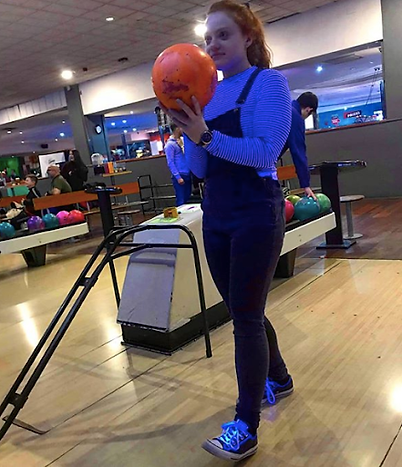 Gina holds an orange bowling ball ready to bowl.