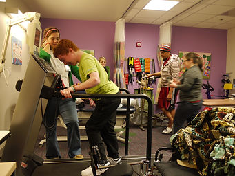 Charlie stands on a treadmill in a therapy room after SDR surgery, his physio stands to the side of him. More people are in the background.