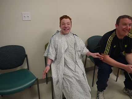A photo of Charlie at 13 years old sat in a hospital waiting room wearing a white medical gown, awaiting his SDR surgery,