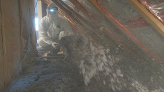 PWC worker blowing instalation in attic.