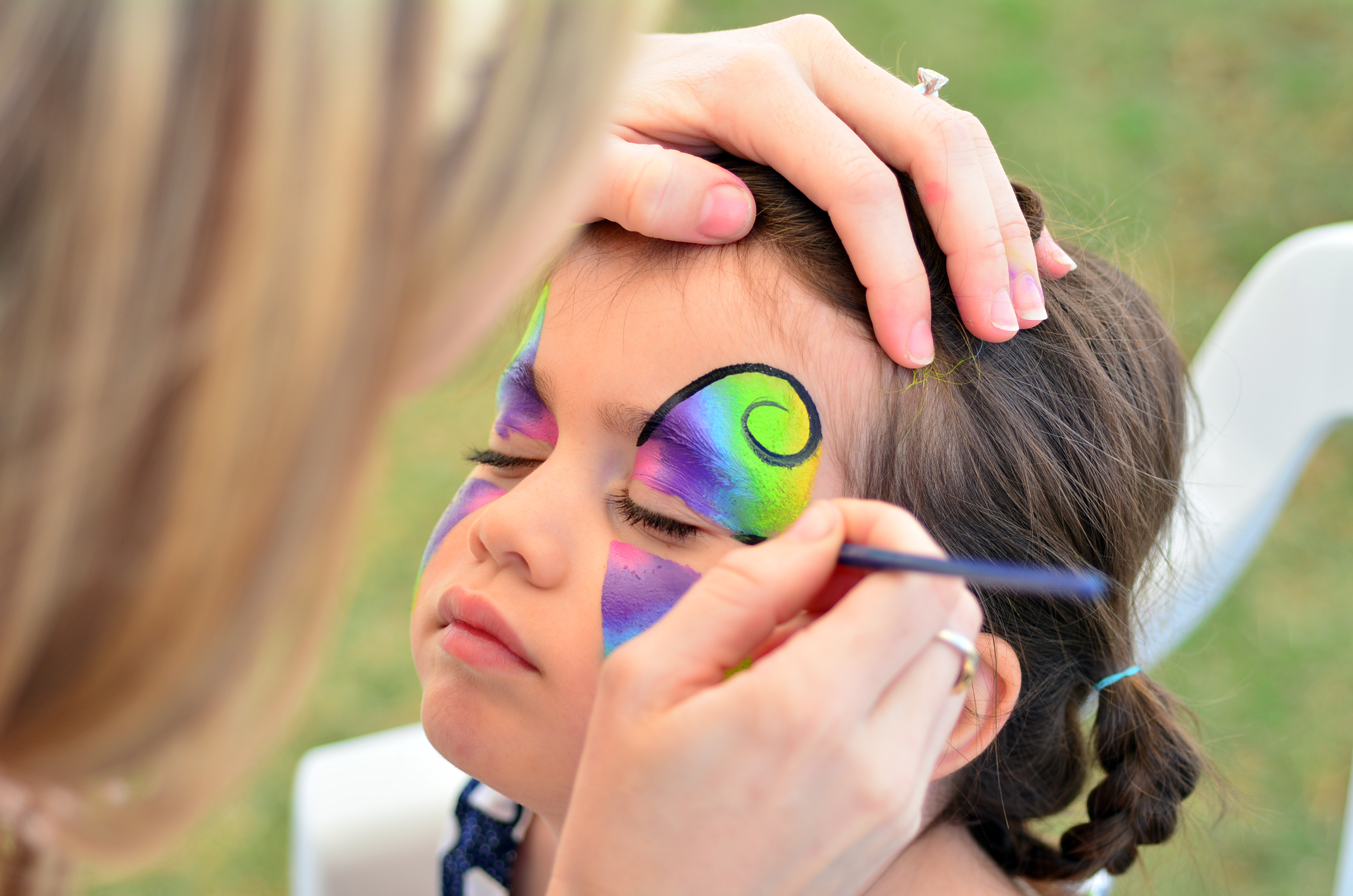 Young girl getting her face painted like