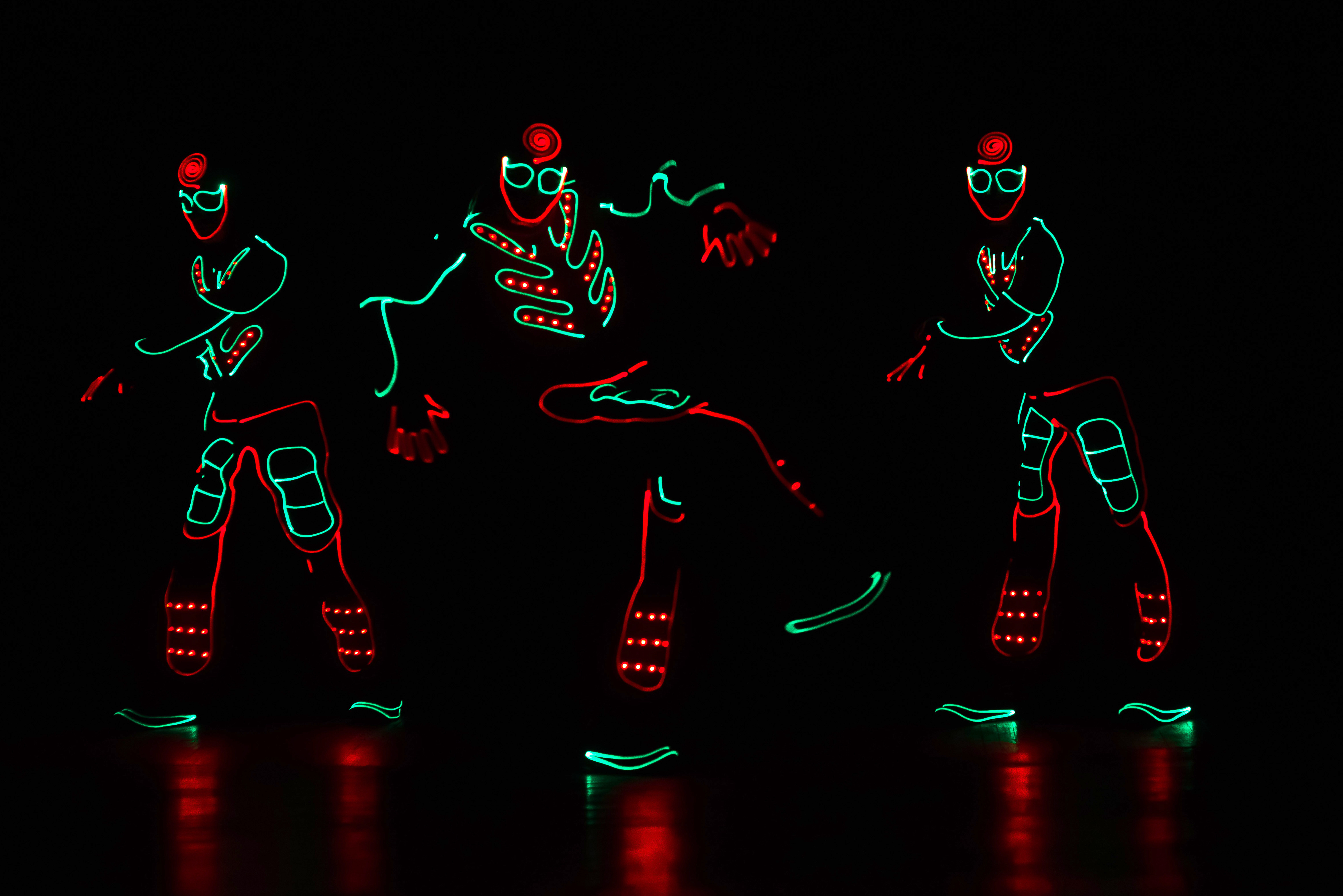 dancers in led suits on dark background,
