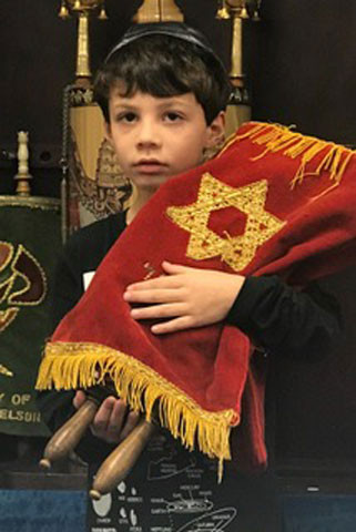 Jared, a student at Solomon Schechter Day School in Chicago, with the little tattooed Torah.