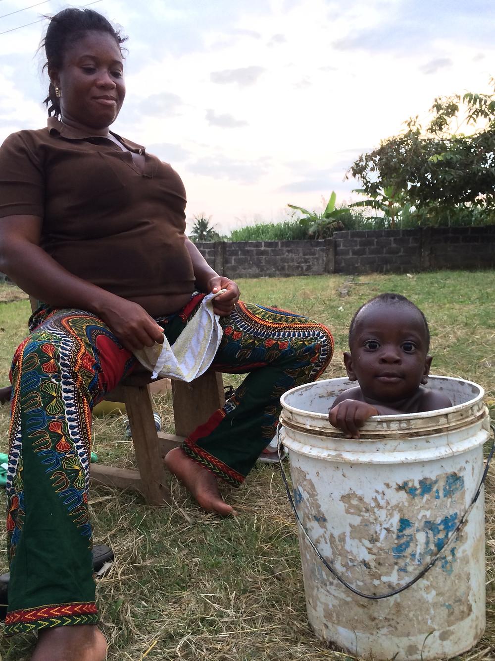 Aunti Akus, cuidadora de los niños del orfanato, baña a su hijo Adwum.